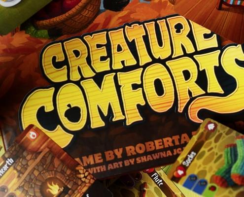 Creature Comforts Schriftzug mit einigen Spielkomponenten